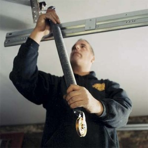 technician performing garage door repair in Toronto area home